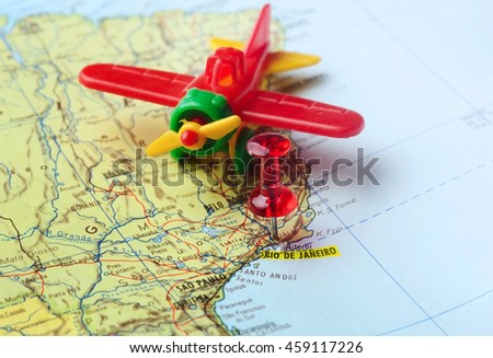 Close-up of a red pushpin on a map of  Rio de Janeiro and airplane  - travel concept