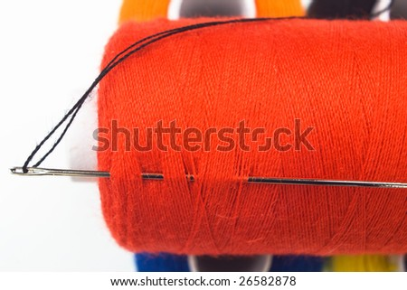 close up of a red sewing spool with a needle