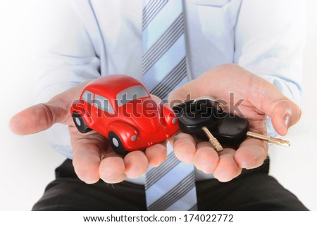 close-up of a red toy car and car keys in the hand of a business man wearing a blue shirt and blue tie on a white background - stock photo