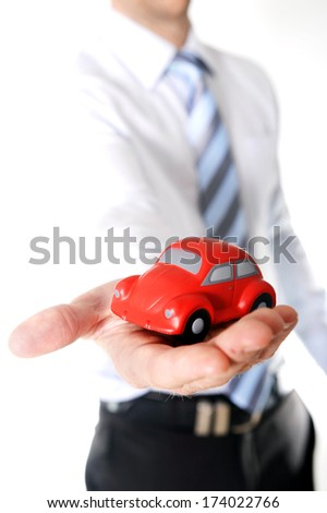close-up of a red toy car in the hand of a business man wearing a blue shirt and blue tie on a white background - stock photo