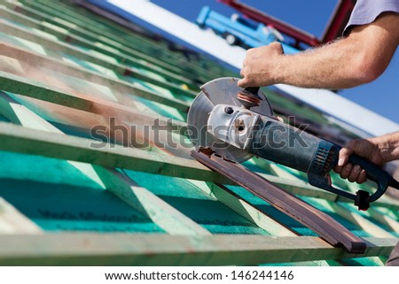 Close-up of a roofer using a hand circular saw to cut a roof-tile - stock photo