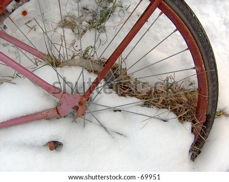 Close up of a rotting bicycle left in the snow. - stock photo