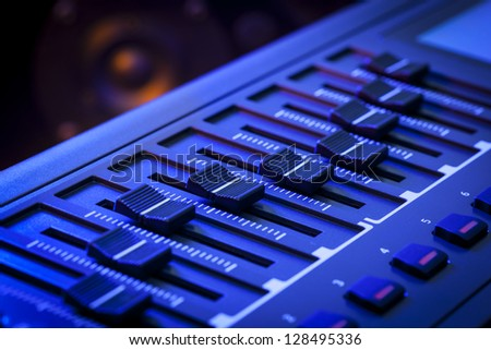 Close-up of a row of faders on a MIDI controller Keyboard with a speaker out of focus in the background. - stock photo
