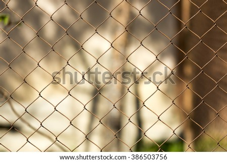 Close-up of a rusty chain-link fence at the corner.