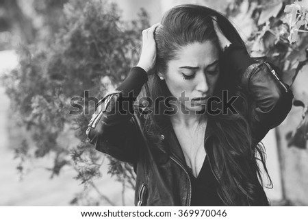 Close-up of a sad and depressed woman deep in thought outdoors. Girl with her hands on head. Black and white photograph. - stock photo