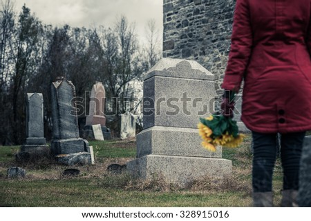 Close-up of a Sad Woman Holding Sunflowers in front of a Loved one's Gravestone. Focus on the Grave. - stock photo