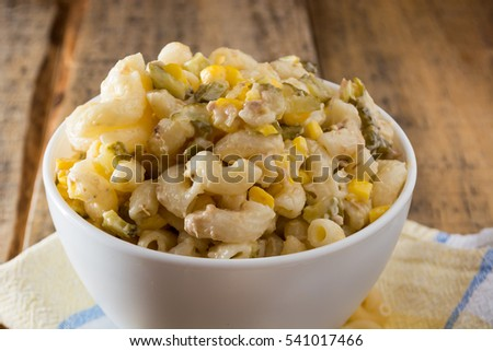 Close up of a salad with pasta, yellow corn and Italian seasonings.