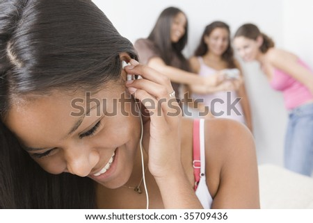 Close-up of a schoolgirl listening to an MP3 player - stock photo