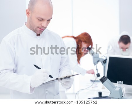 close-up of a scientist taking notes in a chemistry lab and another two students analyzing under microscope in the background around a lab table - stock photo