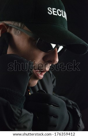 Close-up of a security guard reporting the situation into his microphone. - stock photo