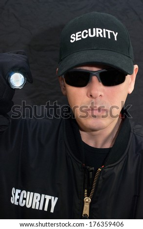 Close-up of a security guard shining a flashlight at the camera. - stock photo