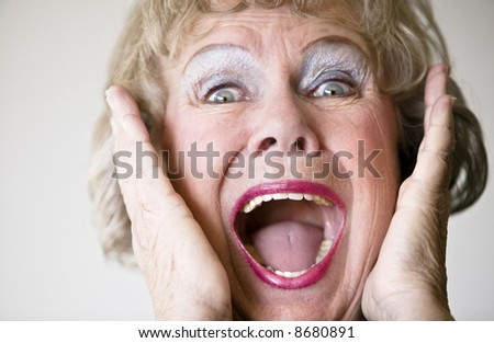 Close-up of a senior woman with her mouth open screaming. - stock photo