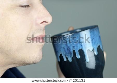 Close-up of a serene man smelling his mug. - stock photo