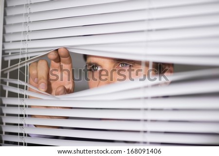 Close-up of a serious young businessman peeking through blinds in the office
