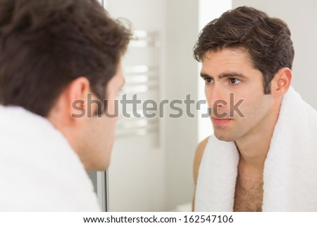 Close up of a serious young man looking at self in mirror in the bathroom - stock photo