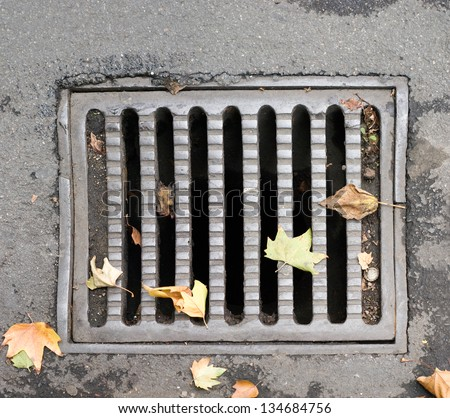 Close-up of a sewer grate, covering a storm-water drain, and a few colorful autumn leaves. High resolution multi-frame composite. - stock photo