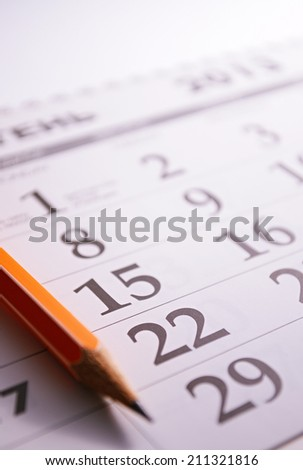 Close-up of a sharp pencil on the page of a calendar, in order to mark days with events - stock photo
