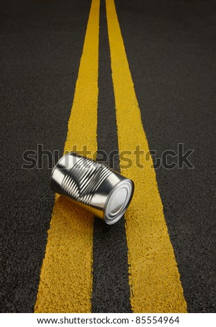 Close up of a shiny dentedl can sitting on a black asphalt road with yellow stripes. - stock photo