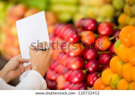 Close up of a shopping list at the grocery store - stock photo