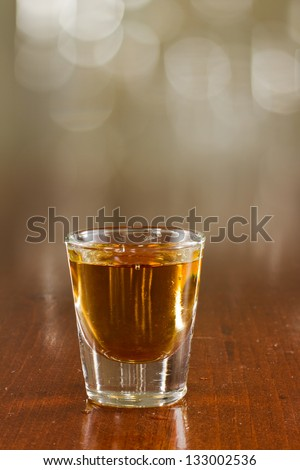 close up of a shot of whiskey on a bar top - stock photo