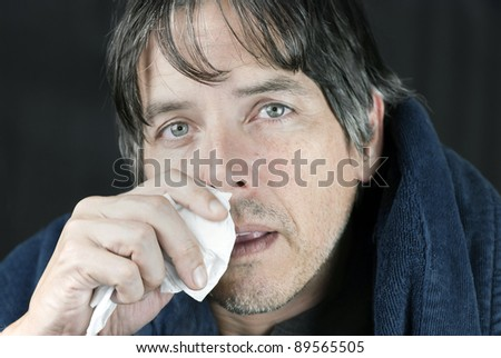 Close-up of a sick man in a housecoat dabbing his runny nose with a tissue. - stock photo