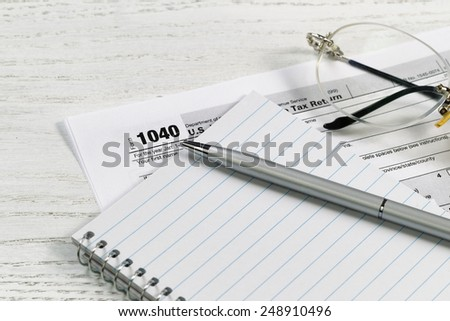 Close up of a silver business pen on top of notepad with tax form and reading glasses in background on white desk. Focus on tip of pen.  - stock photo