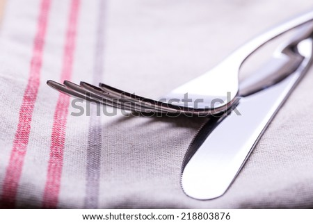 Close up of a silver knife and fork on a white background