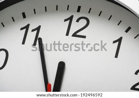 Close up of a simple clock face with the hour and minute hands approaching midnight or twelve o'clock