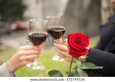 close up of a single rose with a romantic couple drinking wine in the background - stock photo