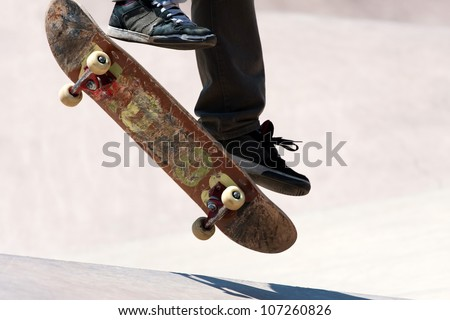 Close up of a skateboarders feet while skating on concrete at the skate park. - stock photo