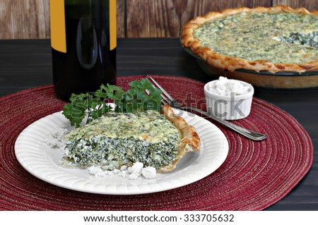 Close up of a slice of spinach and feta quiche in front of the cut pie. - stock photo