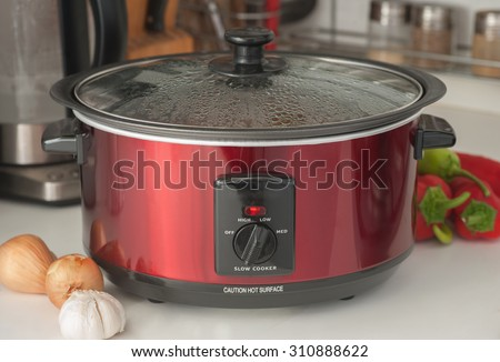 Close up of a slow cooker working on kitchen shelf - stock photo