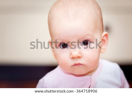 Close-up of a small child who cries but does not scream. A tear rolling down his cheek. Blurred background. Photo girl. - stock photo
