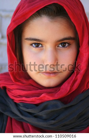 Close-up of a small girl with hijab  (a red headscarf )