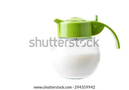 Close up of a small jar or container with milk in it isolated on a white background