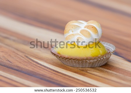 close up of a small lemon meringue on a wooden table - stock photo