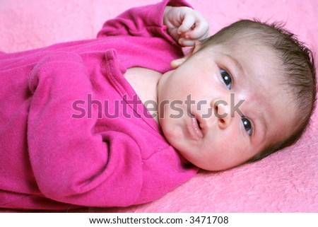 close up of a small one week old newborn baby expression on a pink background - stock photo