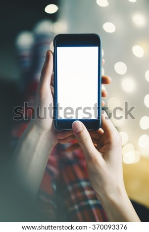 close-up of a smartphone with a blank screen in the hands of a girl in a homely atmosphere background bokeh light - stock photo
