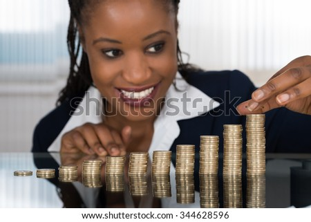 Close-up Of A Smiling African Businesswoman Making Stack Of Coins - stock photo