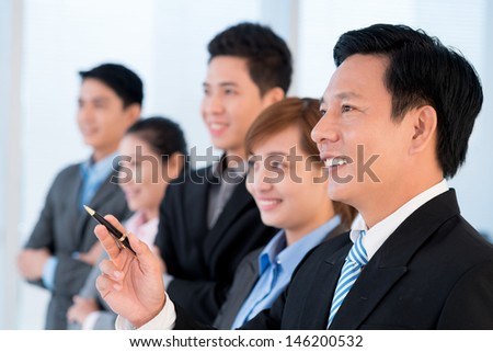 Close-up of a smiling businessman pointing at something on the foreground - stock photo