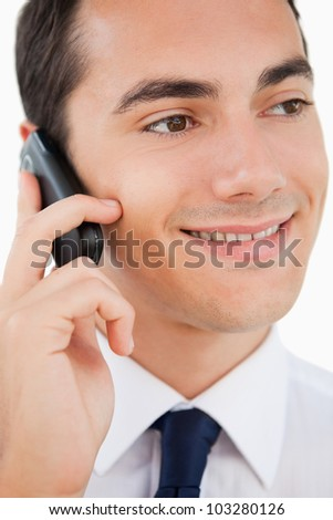 Close-up of a smiling man in a suit using his cellphone against white background
