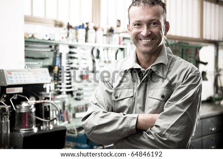 Close-up of a smiling mechanic inside his auto repair shop - stock photo