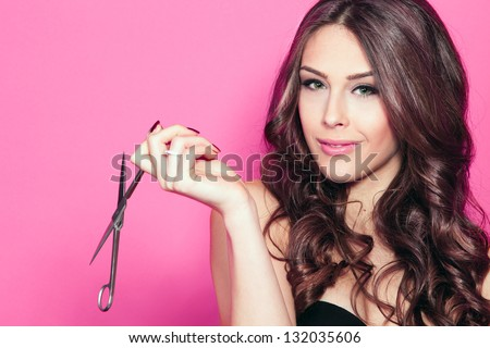 close up of a smiling young woman with beautiful hair, hold scissors in one hand pink background - stock photo