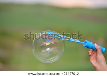 Close up of a soap bubble growing from the blower ring hold by a woman hand over country landscape. With reflection of trees and cloudy sky