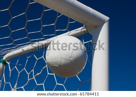 Close-up of a soccer ball (football) going into the top corner of the goal with a blue sky background. - stock photo