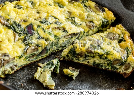 Close up of a spinach mushroom and purple onion frittata in a cast iron skillet pan - stock photo