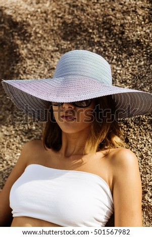 Close up of a sporty lady in white skirt, top, sunglasses and summer straw hat lay on a big rock. Beauty cute girl on a tropical beach sea ocean shore with large stones. Outdoor summer lifestyle.