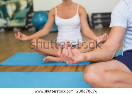Close up of a sporty young couple sitting in lotus posture at fitness studio - stock photo