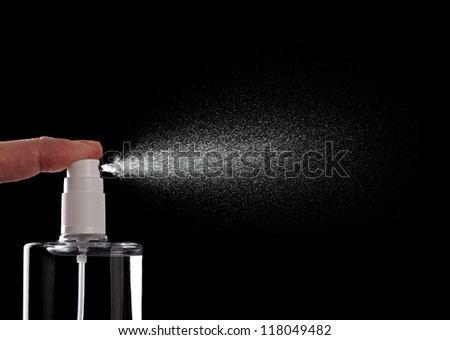 close up of  a spray bottle drops on black background