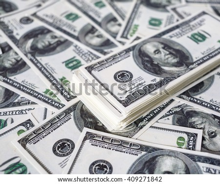 Close-up of a stack of one hundred dollar bills on a background of money. Fake money. Shallow depth of field. Selective focus. - stock photo